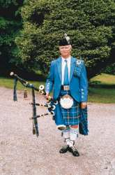 Scottish Piper In Full Dress.