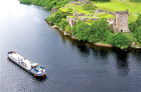 Scottish Highlander cruising on Loch Ness past Urquhart Castle